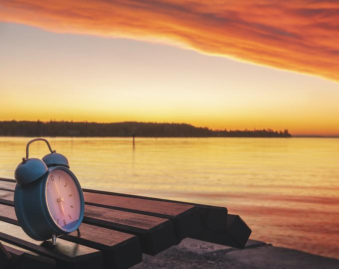 Wecker im Sonnenuntergang früh sparen
